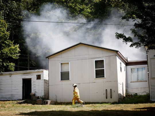 A firefighter walks past the residence at 1 Sitzer Road in Pine City Saturday afternoon as smoke billows from the rear of the home. Multiple fire crews worked together to put out the fire.