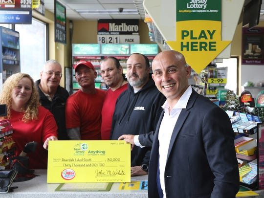 Ameer Krass, owner of Riverdale Lukoil South, poses with some of his employees during a press conference on Monday, April 2, 2018.