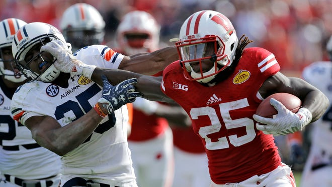 Wisconsin running back Melvin Gordon (25) stiff arms Auburn defensive back Jermaine Whitehead (35) on a 53-yard touchdown run during the third quarter of the Outback Bowl NCAA college football game, Thursday, Jan. 1, 2015, in Tampa, Fla.