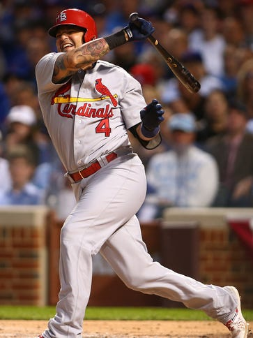 Yadier Molina grimaces on a follow-through in Game