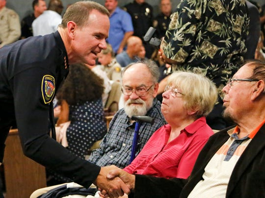 Oxnard Police Chief Scott Whitney, left, speaks with supporters before taking the oath of office at Tuesday night's City Council meeting.