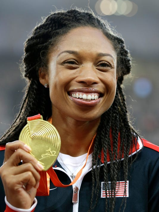 FILE - In this Aug. 28, 2015, file photo, women's 400-meter gold medalist Allyson Felix celebrates on the podium at the World Athletics Championships at the Bird's Nest stadium in Beijing. Felix's training is all geared toward the finish line in the 200 and 400 meters at the Rio Olympics. Schedule allowing, she hopes to be at the starting line for both races. Problem is, those events are scheduled to happen 75 minutes apart. (AP Photo/Kin Cheung, File)