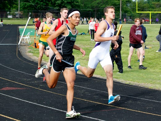 Meade County's Geo Kapalungan (L) and Male High School's Hayden Shelton (R) lead off the start of the mens 4x800 Meter Relay in the Class 3-A Region 3 track and field meet at Fern Creek High School in Louisville, Kentucky.       May 15, 2014