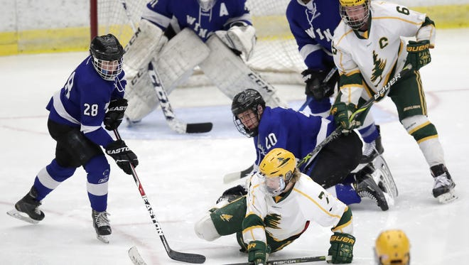 D.C. Everest's Ty Tretter, front, reaches out for the puck during a WIAA state boys hockey quarterfinal game against Waukesha North last Thursday. Tretter assisted on both of the Evergreens' goals in the game.
