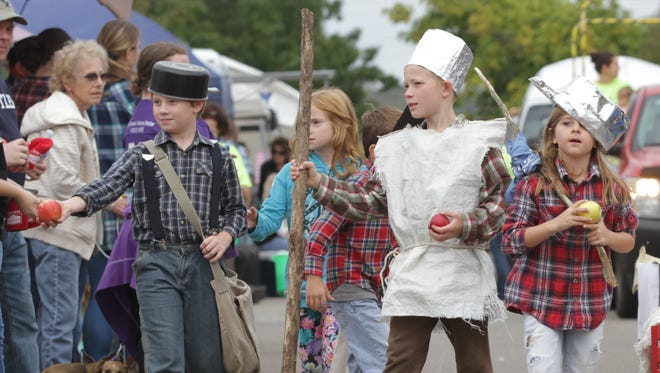 Children from Bultler Elementary School walk down Main Street as part of their town's Apple Festival on Saturday. The kids were dressed as Buckeye pioneer Johnny Appleseed and were handing out apples.