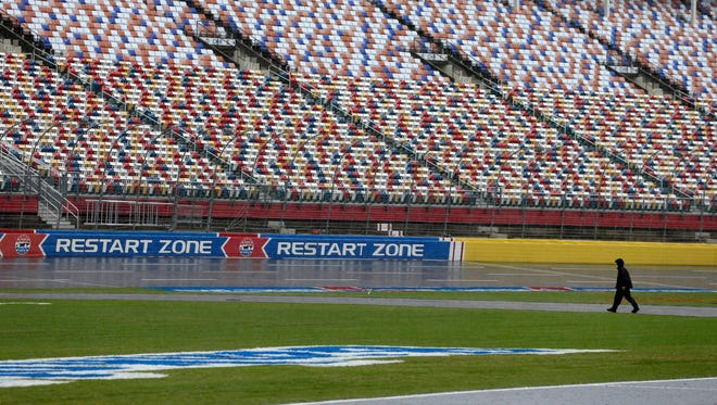 A security guard walks across the track at Charlotte Motor Speedway in Charlotte, N.C., Friday, Oct. 7, 2016.