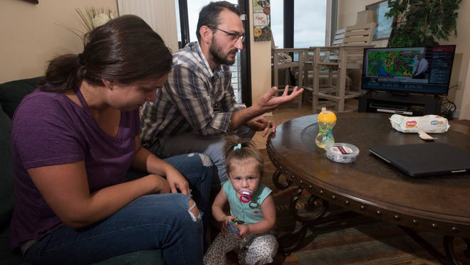 Jen and Rus Fergansky keep tabs on Hurricane Irma while trying to entertain their daughter, Mila, Monday, Sept. 11, 2017. The Jacksonville area couple is seeking refuge from the hurricane at Pensacola Beah after finding a condo free to evacuees on Airbnb.