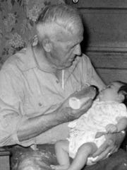 "Even though he was technically the author's great-grandfather, ""Granddaddy"" was the only grandfather she ever knew. Here he is in 1959 giving the author her bottle. Granddaddy passed away when the author was a freshman in college."