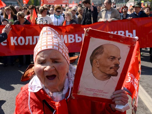 A Russian Communist Party activist carries a portrait of Vladimir Lenin, founder of the former Soviet Union, during a traditional May Day rally in Moscow.