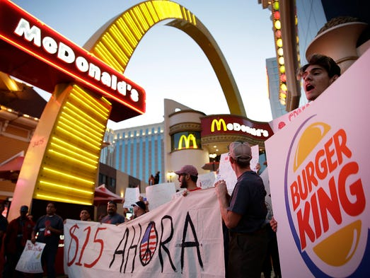 Protestors, including Kris Varrette, right, chant for increased wages and union rights at fast food restaurants Thursday, Sept. 4, 2014, in Las Vegas. Police detained several protesters in cities nationwide Thursday as they blocked traffic in the latest attempt to escalate their efforts to get McDonald's, Burger King and other fast-food companies to pay their employees at least $15 an hour. (AP Photo/John Locher) ORG XMIT: NVJL102