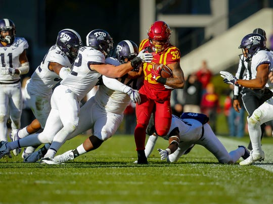 Iowa State Cyclones running back David Montgomery (32) eludes TCU defenders during the first half of their game at Jack Trice Stadium Saturday, Oct. 26, 2017, in Ames, Iowa.