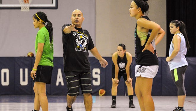 Guam women's national basketball team coach, Eddie Pelkey, instructs team members as they run drills during a practice session at the Academy of Our Lady Guam gym in Hagatna on May 27.