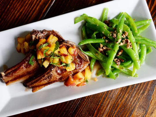 Grilled lamb chops with sweet peach salsa and green beans with jalape–o strawberry vinaigrette and sugared pecans from Sainte Terre.
