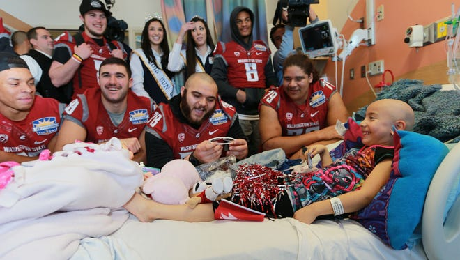 Ayana Jaramillo enjoys a visit by members of the Washington State football team and the Sun Court on Thursday at El Paso Children's Hospital. Carlos Freeman, center, offered Ayana a pair of Washington State sunglasses, which she declined to wear.