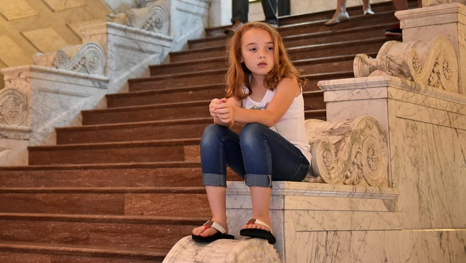 Isabella Nichols, 8, who has Type 1 diabetes, sits inside the state Capitol on Tuesday. For the last three years, Isabella has received supplies for diabetes through Medicaid but recently has had problems with coverage.