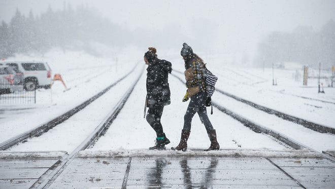 Northern Arizona University students Sonja Usher (left) and Sera Young cross the railroad tracks near downtown Flagstaff during a recent snowstorm. Officials are advising outdoor enthusiasts who want to take advantage of heavy backcountry snow in the Coconino National Forest to get the proper free permit.