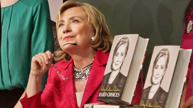 Hillary Rodham Clinton listens before signing a copy of her book Tuesday at a Barnes and Noble bookstore in New York.