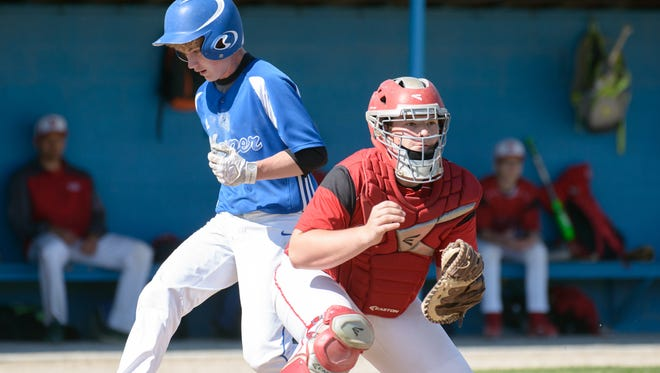 Harper Creek's Drew Mitchell (12) scores early in the second inning.