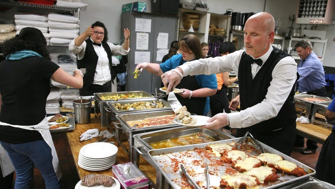 Dan Johnson and the kitchen staff, plate food during an event at The Diplomat Banquet Center in Gates.