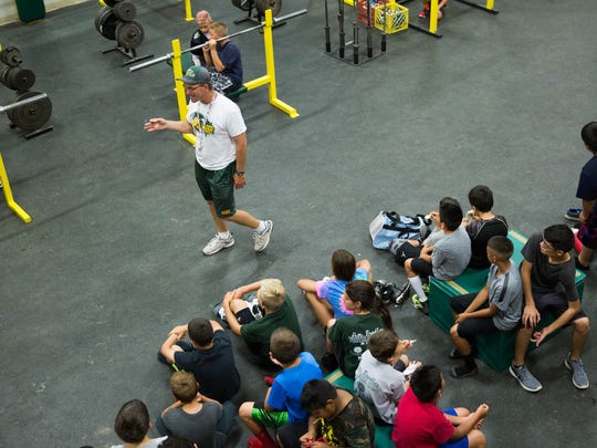Mayfield football coach Michael Bradley, talks to students at the Jim Bradley Football Camp about team work in the weight room at Mayfield High School on Wednesday.