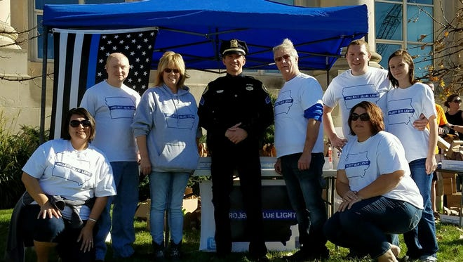 The crew of Project Blue Light Iowa with Des Moines Police Sgt. Paul Parizek on Sunday in front of the Des Moines Police Station. Judi Johnson is in the gray sweatshirt.