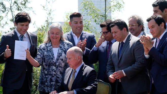 From front left,  California Senate President pro tempore Kevin de Leon, D-Los Angeles, State Sen. Fran Pavley, D-Agoura Hills, Calif., California Gov. Jerry Brown, Assemblyman Eduardo Garcia, D-Coachella, and Assembly Speaker Anthony Rendon, D-Paramount, are congratulated after signing legislation in Los Angeles on Thursday, Sept. 8, 2016. The law sets a new goal to reduce greenhouse gas emissions 40 percent below 1990 levels by 2030.