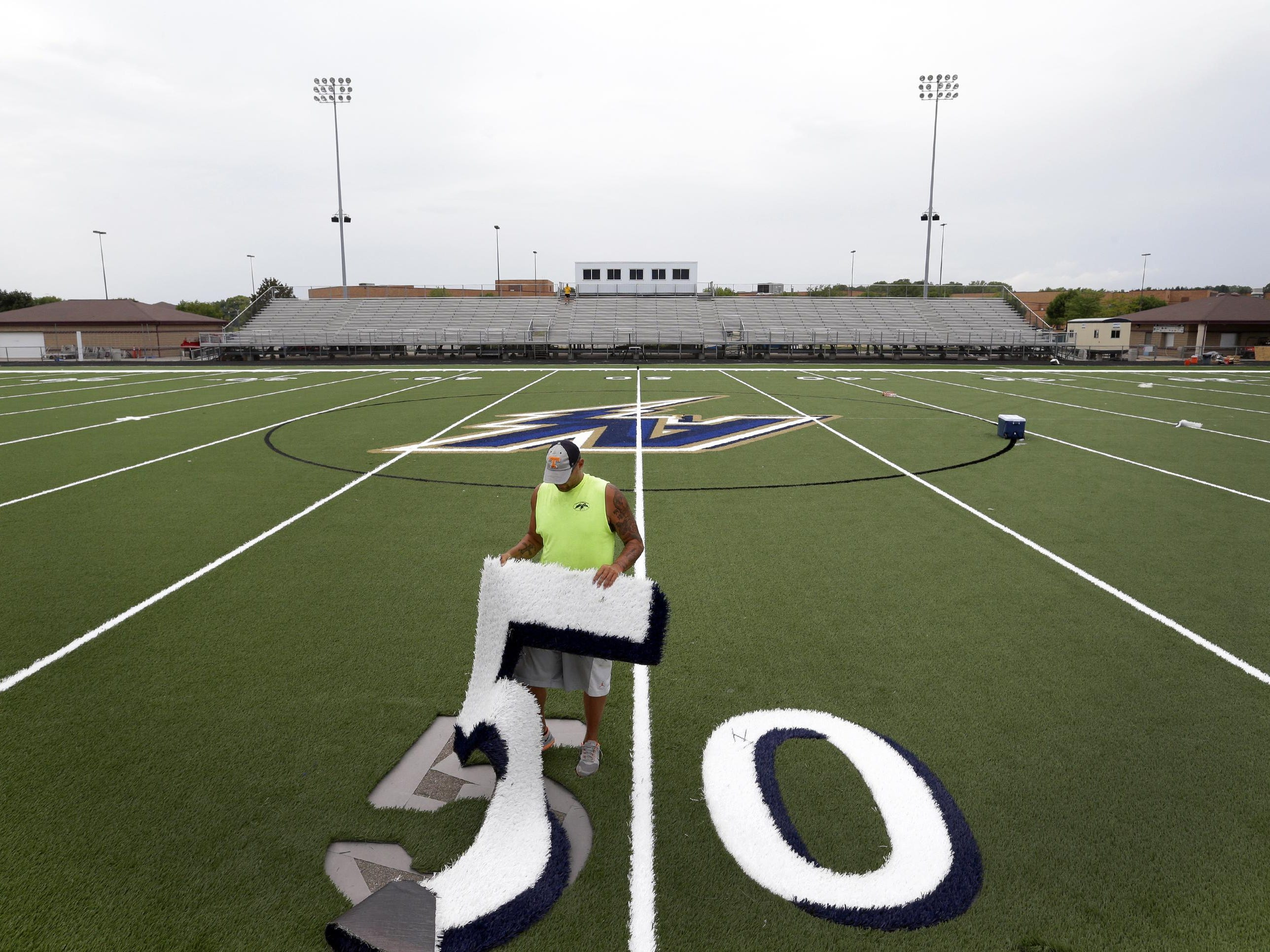 After setting seam tape in preparation for a glue application, Sports Contracting Group employee Sean Young puts a 50-yard mark in place on the new artificial turf Monday at Appleton North High School.