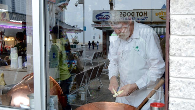 Dick Smith slices butter into an old fashion copper kettle. Those walking by on the boardwalk can watch Smith cook, making small batches of Dolle's caramel popcorn.