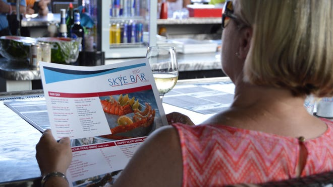 A woman looks over the Skye Bar's menu.