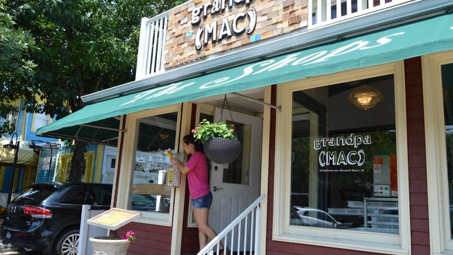 An employee stuffs menus outside grandpa(MAC) restaurant, a new gourmet pasta carryout located in downtown Rehoboth.