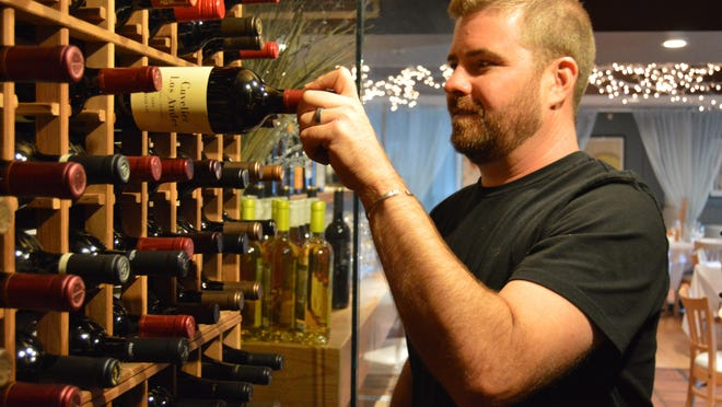 Chris Capriotti selects a bottle from Eden's wine cellar.