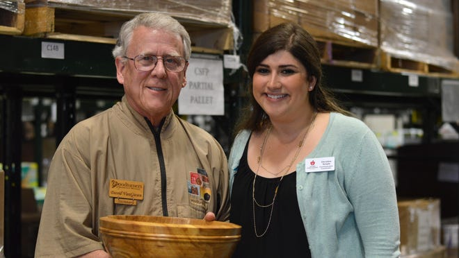 Woodturner David Van Giesen and Ozarks Food Harvest communications coordinator Christine Temple pose with a bowl made from a 130-year-old elm tree removed from Fassnight Park. The bowl will be up for silent auction at the Empty Bowls event 5-8 p.m. Friday at Panera, 2924 E. Sunshine St.