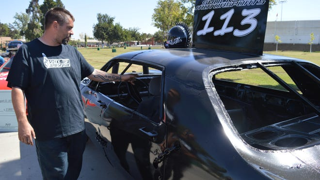 Eric Rossiter walks by the vehicle he will drive in the Tulare County Fair destruction derby.