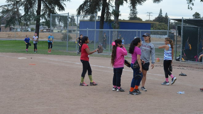 Brianna Stephens warms up during a youth softball team practice Thursday in Tulare.