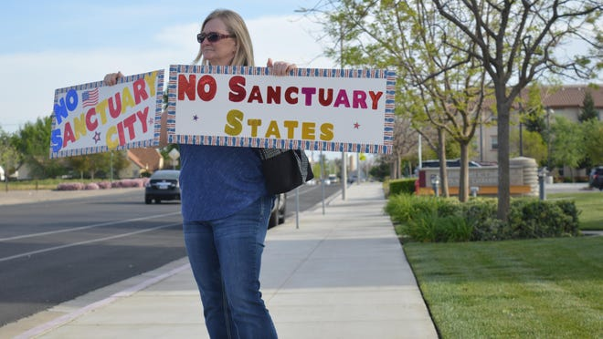 Teresa Avila, of Tulare, holds a sign at Cross Avenue and M Street in protest Tuesday afternoon ahead of the Tulare council meeting to consider State Bill 54, known as the California Values Act. In essence, this bill calls for California to become a sanctuary state. The proposed support for the bill was voted down Tuesday.