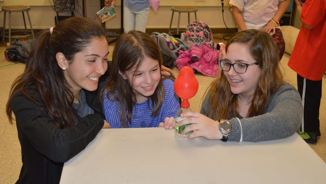 Randolph High School Science Honor Society members and juniors Brooke Olson and Perri Gish work with Center Grove third grader and Girl Scout Emma Maqsudi on an experiment where they blew up a balloon using vinegar and baking soda.