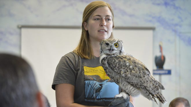 Corrine Coffman, with the Bureau of Land Management-operated Morley Nelson Snake River Birds of Prey National Conservation Area, holds Great Horned Owl, Archimedes, as inmates from Snake River Correctional Institution look on.