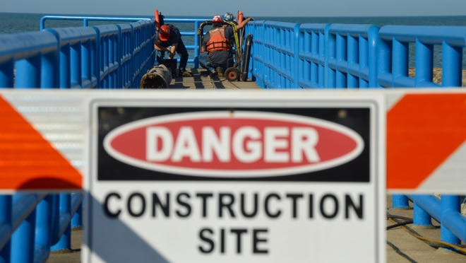 A crew from The King Company begins work on installing a safety gate Monday, Nov. 9, along the pier at Holland State Park.
