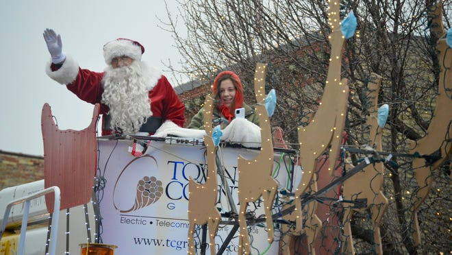 Santa Claus waves to the crowd during his Saturday, Dec. 19, visit to downtown Zeeland, courtesy of Town and Country Group.