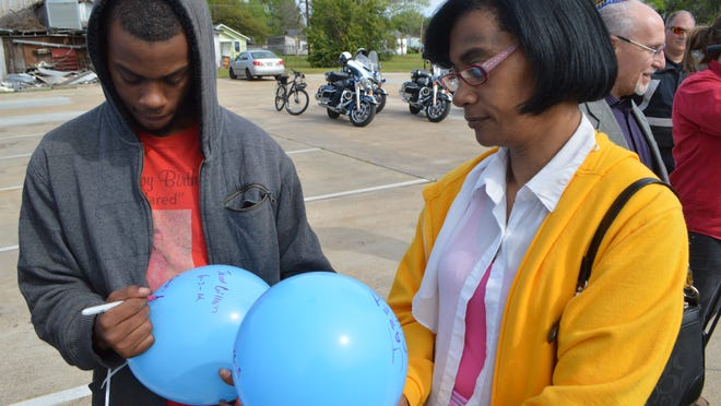 Jordan Gillam (left) and his mother, Gloria Abraham, write messages on balloons during last year's Victims Rights Parade for the late Jared Gillam, who was slain in 2012. The second annual parade will be held Saturday in downtown Alexandria.