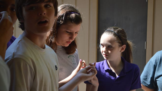 (From left) Devan Ryder, 15, and Savannah Smith and Kayla Fletcher, both 14, pass around and examine a fired bullet to see how it changes once it impacts something. The Montgomery High School freshmen were at Camp Grant Walker on Wednesday to learn about gun safety, as well as other topics.