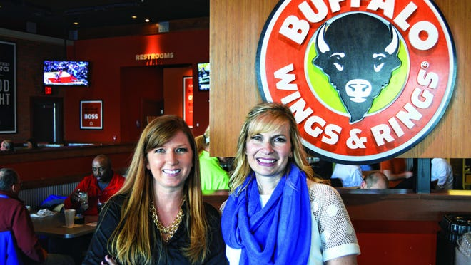 Marketing manager Lindsey Case, left, and marketing director Diane Matheson, right, show off Buffalo Wings & Rings' new look.