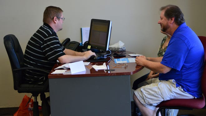 Jeff Heath, left, tax specialist with Jackson Hewitt, works with Matt and Shauna Thorne to prepare their taxes in March of 2015.