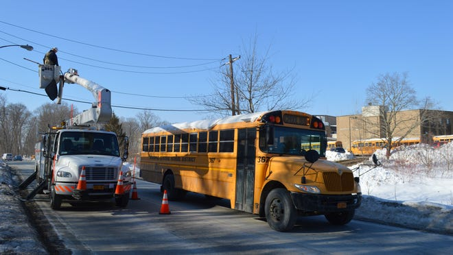 A Mahopac school bus pulls by a utility truck on Baldwin Place Road as students at Mahopac High were dismissed at 9:30 a.m., due to loss of power. Crews have been working to restore power since Sunday.