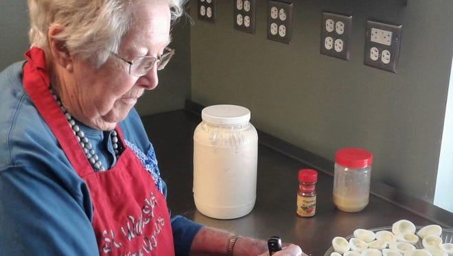 No stranger to kitchen work, Mary Hurt is shown whipping up deviled eggs April 24 as a volunteer for the Free Lunch Program of Iowa City. She will celebrate an amazing 100 years of life on May 5.