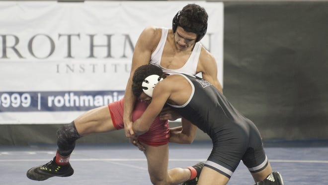 Delsea's Edison Echevarria, left, defends against a take down attempt by Egg Harbor Township's Terrell Coleman during the 120-pound preliminaries on Friday at Boardwalk Hall in Atlantic City.