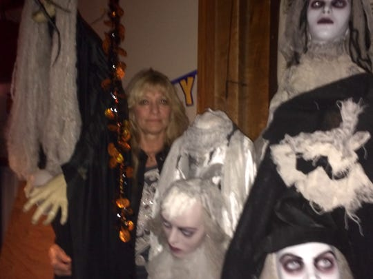 Owner Carol Kruse stands among some of the many ghouls that decorate BC's Saloon. It's been a tradition for more than 20 years for her to deck the neighborhood bar on Lime Kiln Road out for Halloween.