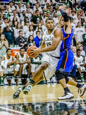 Marvin Clark ,left, of MSU drives the baseline to the basket around Chris Chiozza of Florida on his adding 2 points to the Spartan effort Saturday December 12, 2015 in East Lansing. KEVIN W. FOWLER PHOTO
