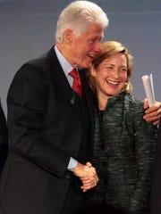 Former President Bill Clinton hugs Dr. Meredith Rosenthal,