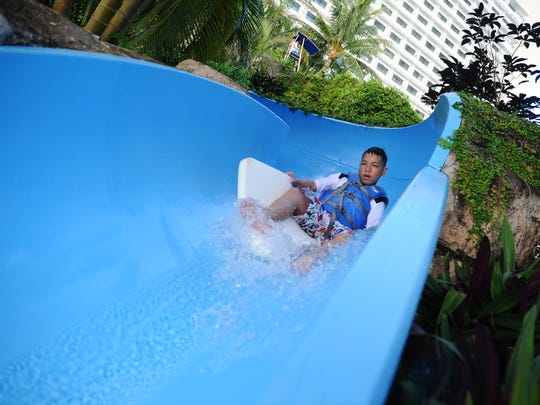 Wish kid Miguel Rosario, 12, splashes down a water slide at the Pacific Islands Club Guam water park on July 31, 2015. A weekend stay at the Tumon hotel was a wish granted to him by the Make-A-Wish Foundation of Guam.